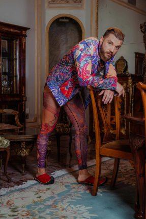 הוא בטייץ מקועקע חצי שקוף לגבר עם חלק עליון אטום בגזרת ספידו עם ז'קט אופנוענים מקועקע צבעוניים (צילום: תום חוליגנוב).